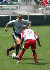 Soccer player attempting to dribble the ball past a defender